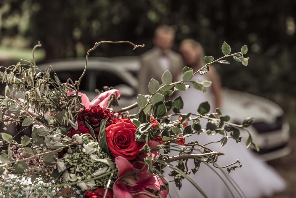 Bryllupsbillede af brudebuket med brudepar i baggrunden