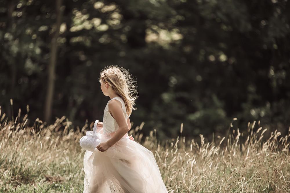 Bryllupsfoto af blomsterpige i naturen til udendørs vielse