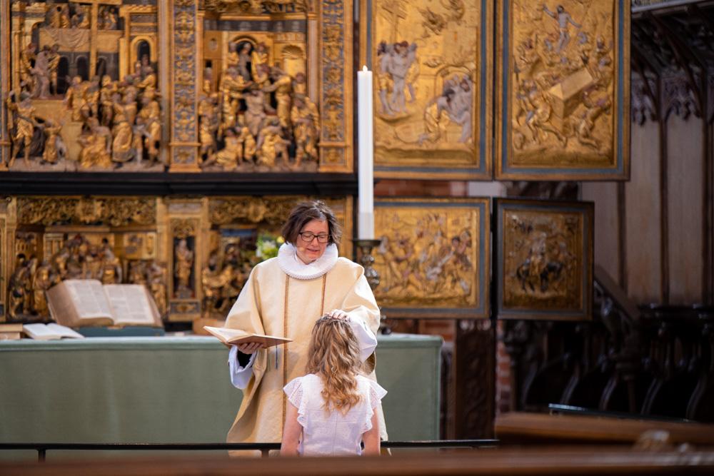 Pige der bliver konfirmeret af præst i kirke