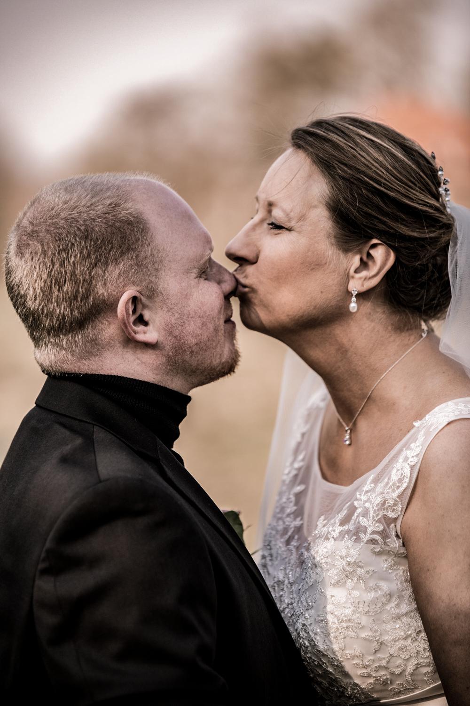Bryllupsbillede af brud der kysser sin gom
