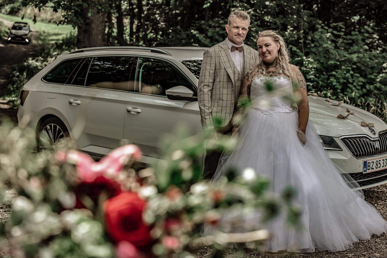 Brudepar foran bryllupsbil i en skov