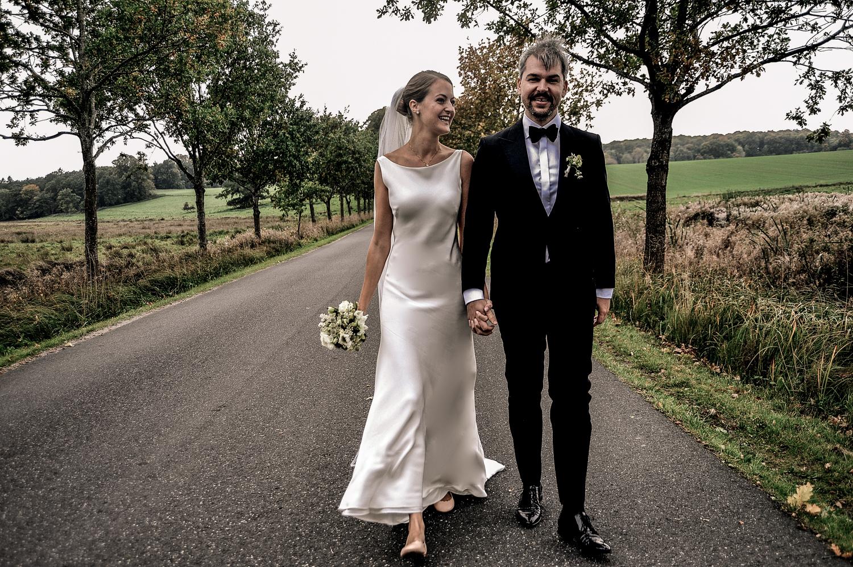 Brudepar hånd i hånd går på en vej og marker