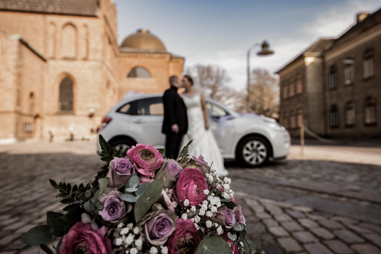 Brudepar der kysser i baggrunden med brudebuket foran