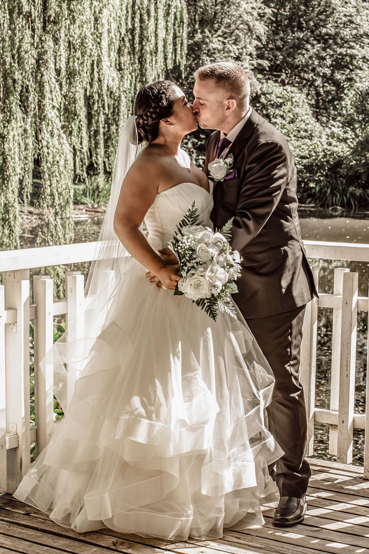 Bryllupsbillede af brudepar der kysser i naturen
